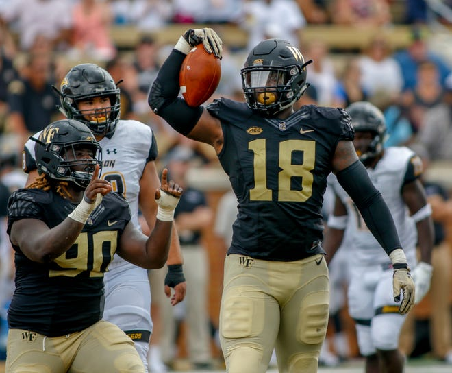 Wake Forest defensive linemen Carlos Basham, right, and Sulaiman Kamara celebrate after sacking Towson quarterback Tom Flacco in a 2018 game.