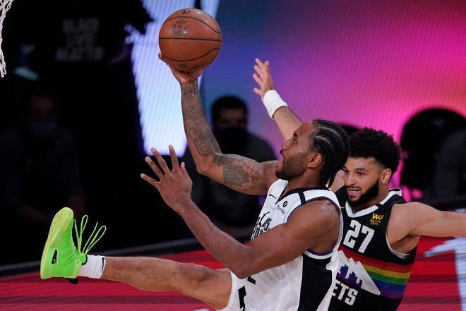 Los Angeles Clippers' Kawhi Leonard drives to the basket past Denver Nuggets' Jamal Murray (27) during the second half  Wednesday, Sept. 9, 2020, in Lake Buena Vista, Fla.
