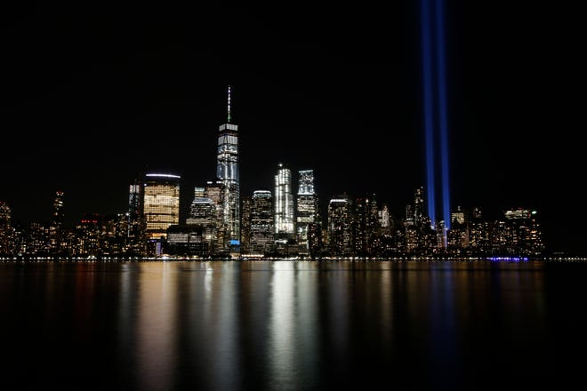 In this Sept. 11, 2017, file photo, the Tribute in Light illuminates in the sky above the Lower Manhattan area of New York, as seen from across the Hudson River in Jersey City, N.J. The terror attacks' 19th anniversary will be marked Friday, Sept. 11, 2020, by dueling ceremonies at the Sept. 11 memorial plaza and a corner nearby in New York.