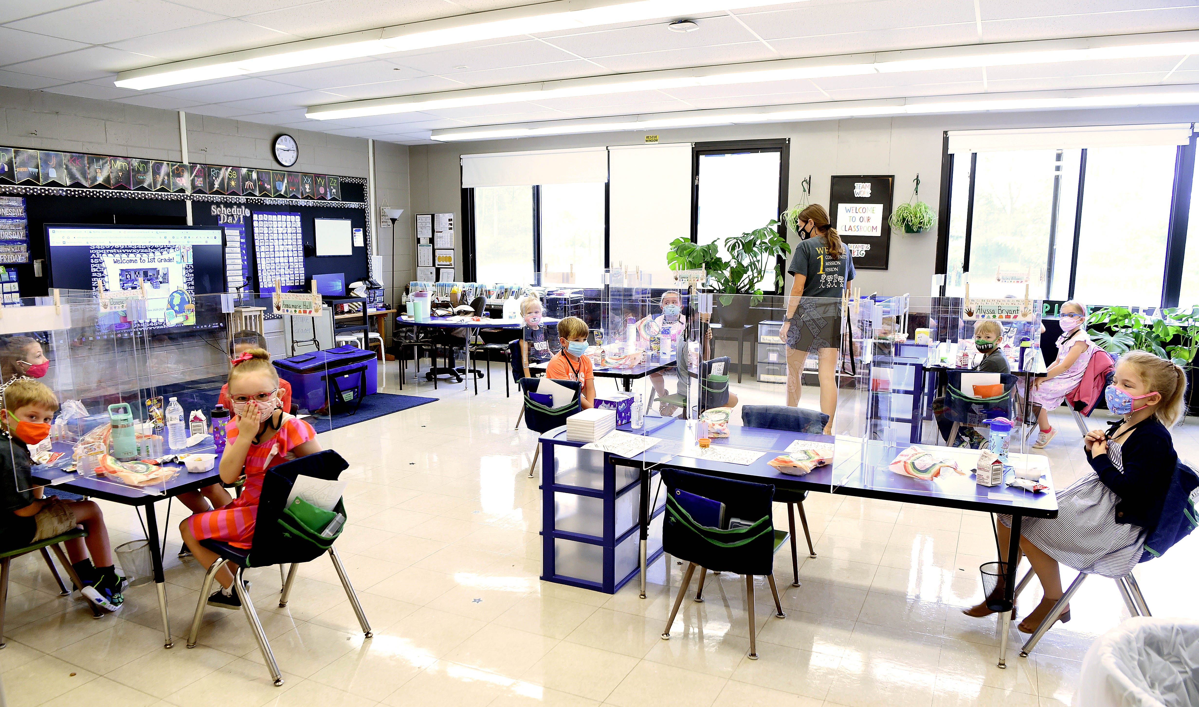 Schools opened in the fall of 2020 like any other year, but pandemic classrooms were unfamiliar to returning students. Here a Windsor first-grade class sits down for breakfast in September wearing masks, at tables spread apart, separated from their classmates by plexiglass partitions.