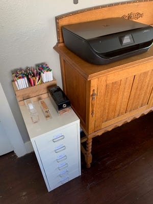 Labeled drawers, automatic pencil sharpener, tape dispenser, stapler and other shared supplies are in a central place in the home.