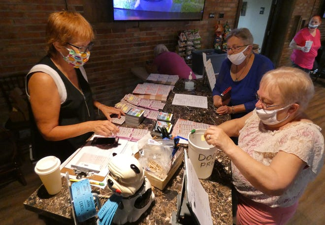DebbiGifford sells bingo cards to D'Aunn Sallee and Bea Benedict, from left, as they prepare for an evening of bingo Wednesday at theHumane Society Serving Crawford County's weekly bingo game.