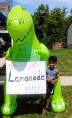 Cayden Cummings used this dinosaur to draw attention to his lemonade stand.