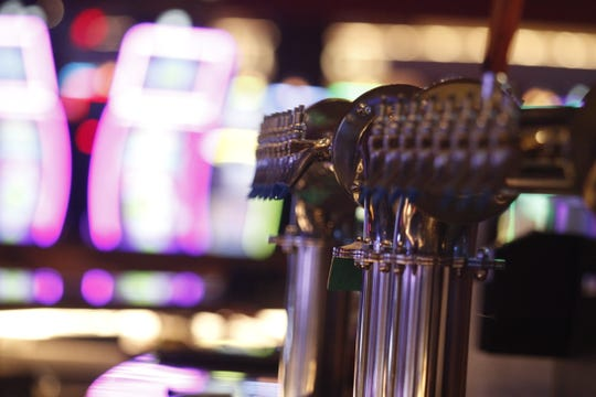 Beer taps shine on a bar amid the glow of gaming machines in the Oak Grove Racing & Gaming facility, set to open to the public on Sept. 18, 2020.