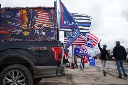 Flags fly on the back of trucks while waiting to hear President Donald Trump speak during a campaign stop at Avflight Saginaw in Freeland on Thursday, September 10, 2020.