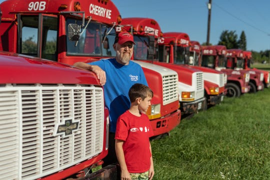 Cherry Ke CFO Nels Veliquette and his son Axel pose for a photo amongst converted school buses used to haul fruit at his cherry farm in Kewadin on Friday, September 4, 2020.Veliquette was featured in an ad by Gary Peters campaign ad speaking about farmers' products that have been threatened by cheap cherries imported from Poland and Turkey, and - it's charged - are now being trans-shipped through Brazil to evade duties.