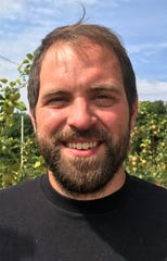 """Fourth-generation cherry grower Isaiah Wunsch, who farms north of Traverse City, stands on Sept. 1, 2020, in front of apple trees he increasingly grows because he says the future of tart cherry farming is """"on the ropes."""""""