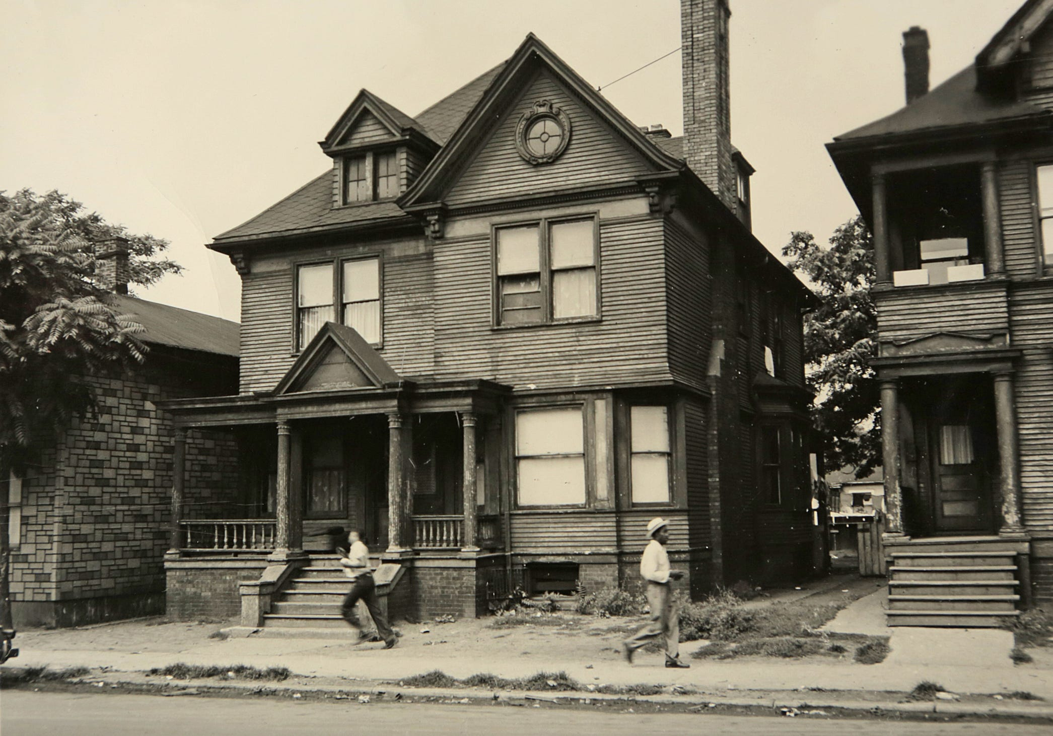 This is a historical photo of Black Bottom before it was torn down in the 1950s to make way for the Chrysler Freeway and the Detroit Medical Center. In this photo two men pass 1535 Monroe St. on August 31, 1949 in Black Bottom, the ancestral neighborhood of many metro Detroit African Americans. Courtesy of the Burton Historical Collection