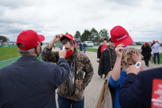 People have their temperature checked while waiting to hear President Donald Trump speak during a campaign stop at Avflight Saginaw in Freeland on Thursday, September 10, 2020.