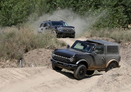 A 2021 Ford Bronco four-door follows a Bronco two-door around the course during the 2020 Bronco Day event at the soon-to-be-opening Holly Oaks Off-road Park in Holly, Michigan, on August 11, 2020. The media were driven around in a variety of 2021 Ford Broncos during the event.