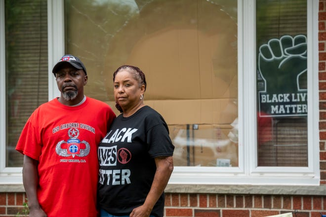 Eddie Hall Jr. and his wife Candace stand in front of the broken front window of their Warren home, September 10, 2020. In an attack on the home a large rock was thrown through the window, racial threats were written on their car and several tires were slashed.