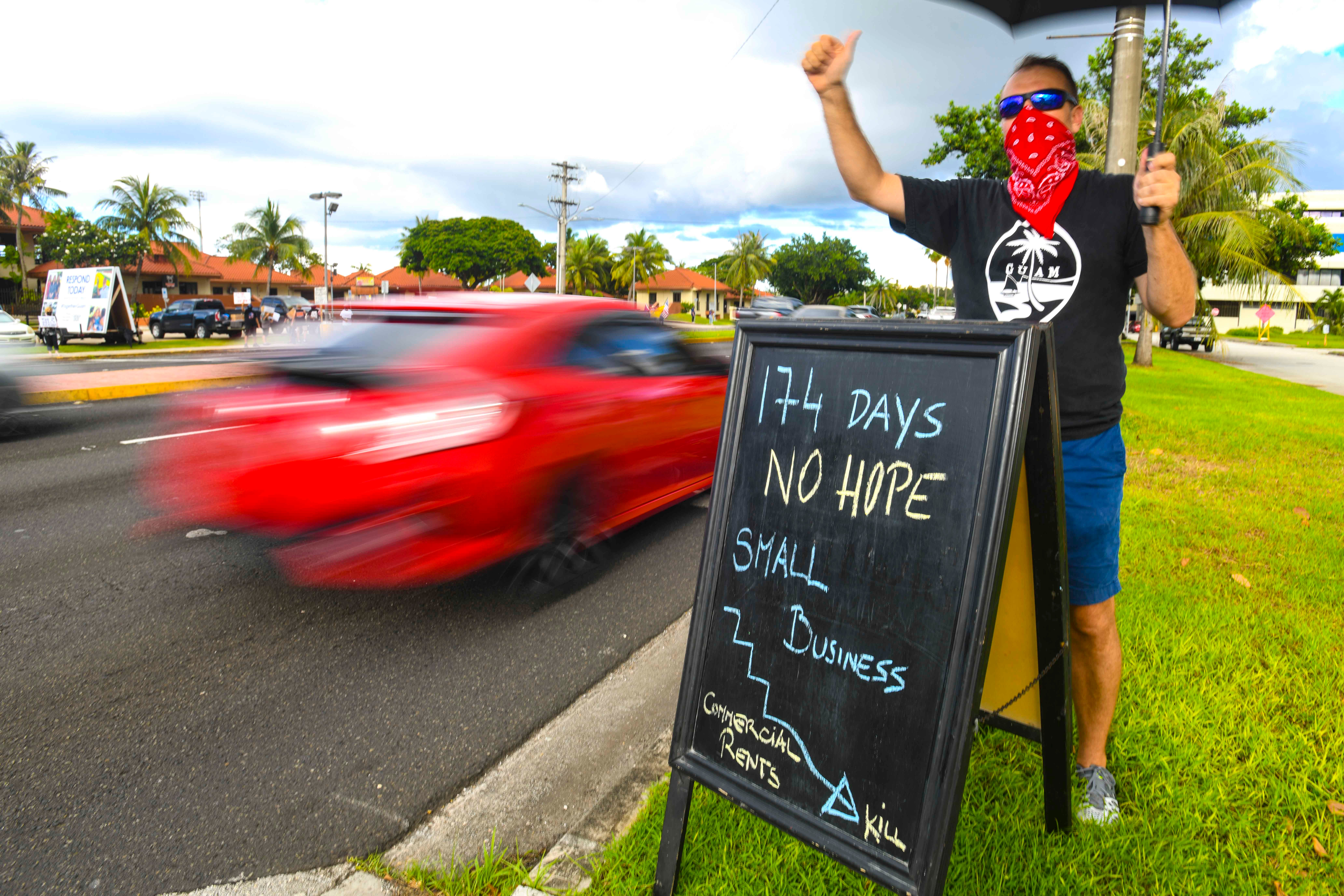 Thomas Peinhopf and other protesters wave during a peaceful protest against pandemic restrictions held along Marine Corps Drive near the CHamoru Village in this Sept. 10, 2020, file photo. According toPeinhopf, neither federal nor local support has been enough to help businesses shuttered because of pandemic restrictions.