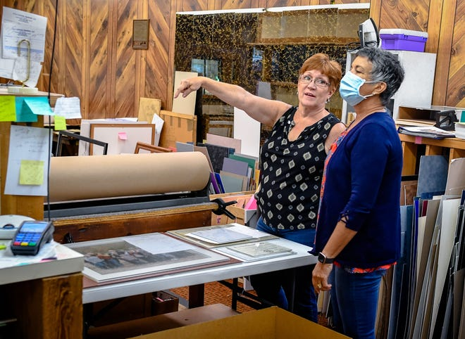 Lisa Baird, owner of C&C Custom Framing, points out picture frame samples to be removed, to friend Lorna Littrell who is helping with the close-out of the shop she has run for 16 years, Tuesday, September 8, 2020.
