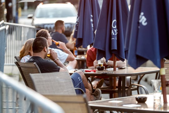 Broad Ripple Tavern patrons sit outside, Wednesday, Sept. 9, 2020. Broad Ripple Avenue re-opened to car traffic after Labor Day, but many bars and restaurants have kept their outdoor seating.