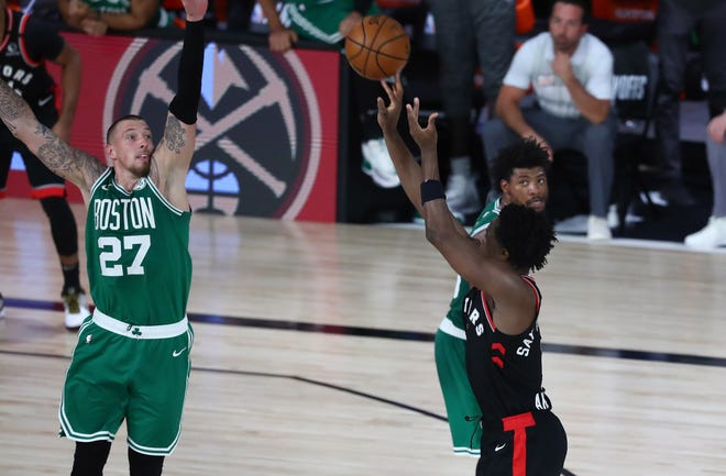 Sep 9, 2020; Lake Buena Vista, Florida, USA; Toronto Raptors forward OG Anunoby (3) makes a three pointer against Boston Celtics center Daniel Theis (27) in the second overtime period in game six of the second round of the 2020 NBA Playoffs at ESPN Wide World of Sports Complex.