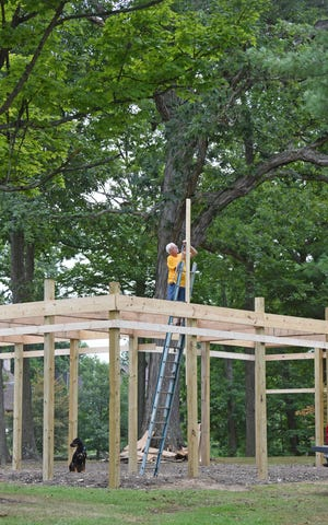 Denny Spangler works on the construction of the new blacksmith and woodworking building Thursday afternoon at South Park.