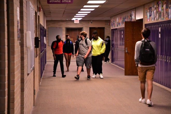 Masked students pass between classes at Central High School.