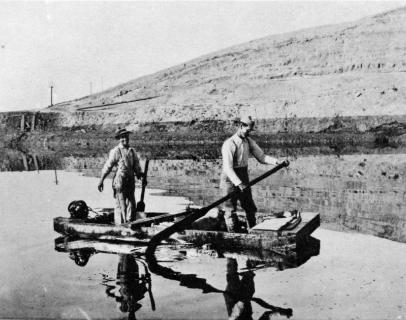 Men row on the lake of oil created by the 1910 Lakeview Gusher.