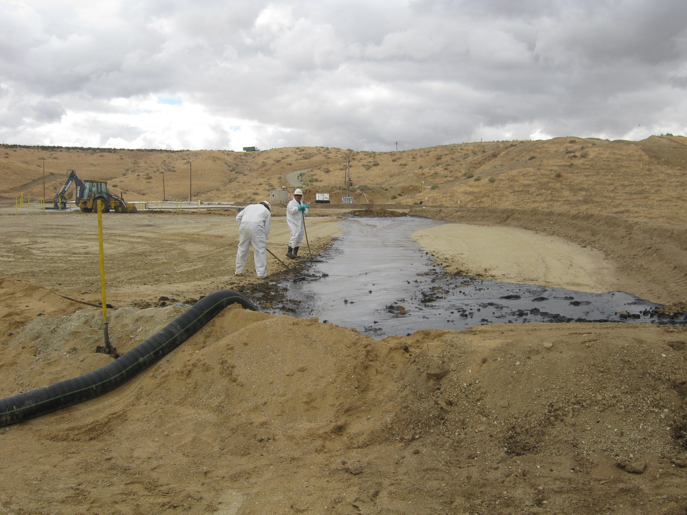 Workers clean up a surface expression in October 2011 in a Kern County oil field, where Berry Petroleum operated. Oil spills can pose long- and short-term health risks for workers.