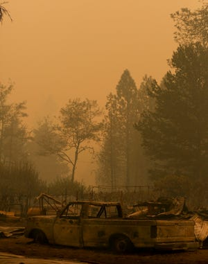 A scorched truck is pictured as smoke hangs heavy in the air caused by the Santiam Fire in Lyons, Oregon on Wednesday, Sept. 9, 2020.
