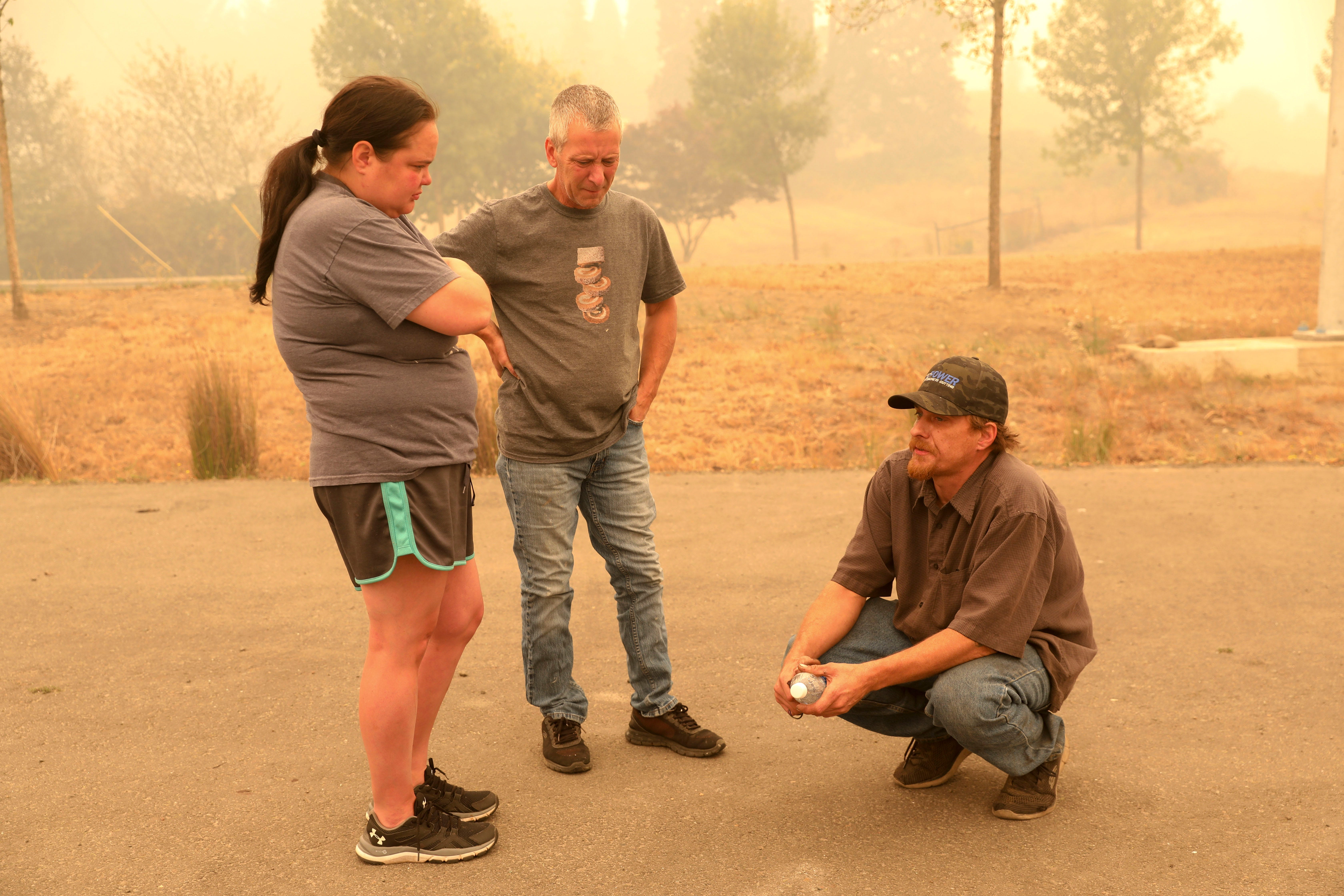 Chris Tofte, right, talks to Miranda Sexton and Troy Ost after a group of volunteers left to continue searching for his son Wyatt Tofte,13, and his dog Duke in Stayton, Oregon on Wednesday, Sept. 9, 2020.