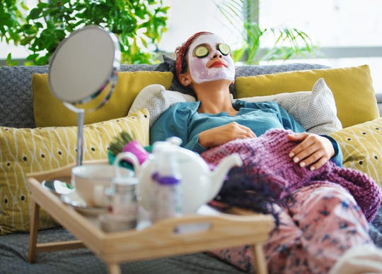 A woman with a mask and rolls of cucumber on her face enjoys a quiet morning