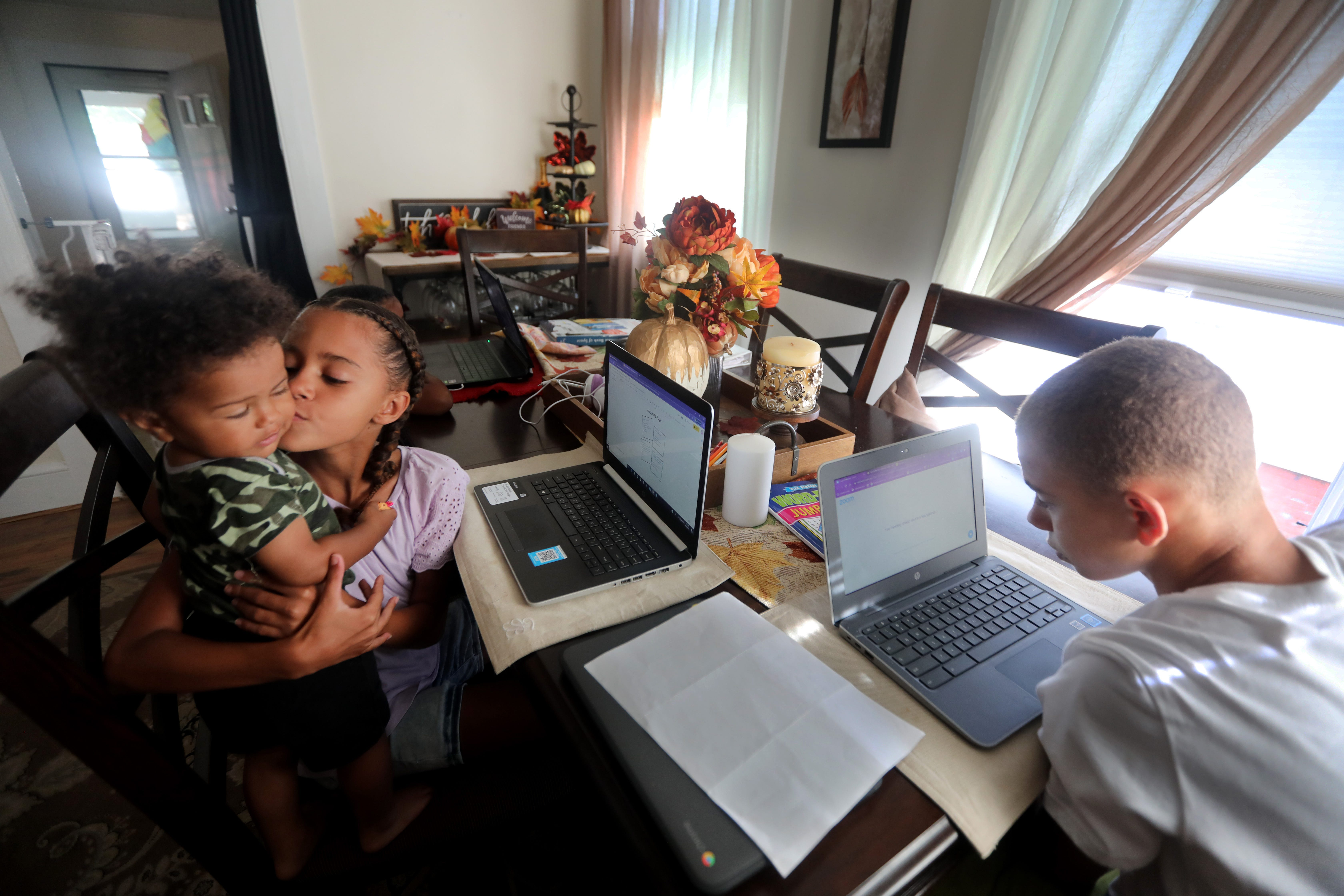 Families juggling remote learning for the first time faced a difficult learning curve. Here Leighann Jansen, 9, a fourth-grade student in Middletown, takes a moment from her work on the first day of school to kiss her 1-year old brother, Luca. There are seven people in the Jansen family, and remote learning has made multitasking essential.