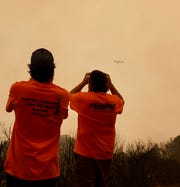 Matt Marvin, left, and Ray Slocum watch as a 747 aerial firefighting tanker prepares to drop retardant on a hot spot on the Creek Fire near Shaver Lake, California, on Sept. 9, 2020. The 747 is known as the Global Supertanker, and it is the world's largest aerial firefighting tanker.