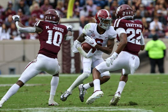 Alabama wide receiver DeVonta Smith (6) runs after a catch while being pursued by Texas A&M defensive backs Clifford Chattman (22) and Myles Jones.