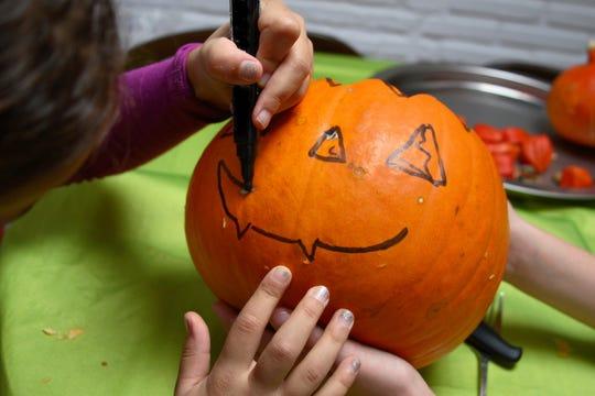 Children give a pumpkin a wide grin.