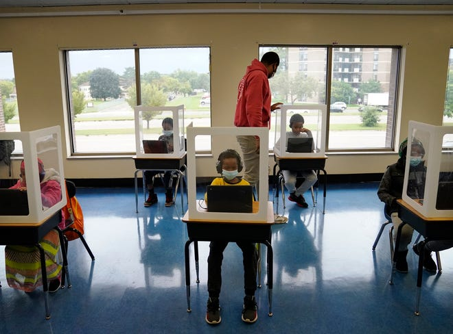 Paraprofessional Jaevon Walton, center, reminds a student to wear his face mask in a learning pod of second through seventh graders at Harvest Best Academy, Tuesday, Sept. 8, 2020, in Minneapolis.