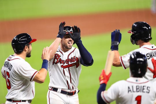 Adam Duvall of the Atlanta Braves celebrates with his teammates after hitting a grand slam during the seventh inning of a game against the Miami Marlins.