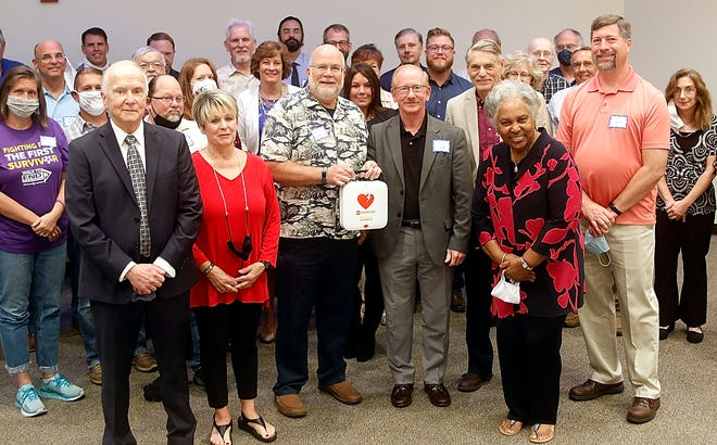 Samaritan Hospital Foundation president Dick Beal, director of grants and community relations Mona Campbell pose for a photo with Ashland County Ministerial Association's Keith Tyson, John Bouquet, Jon Hall and Scot Myers, along with Samaritan Hospital Foundation board member Melody Barnes, with one of the 105 AEDs on Friday the SHF is providing for the 105 Ashland County area churches.