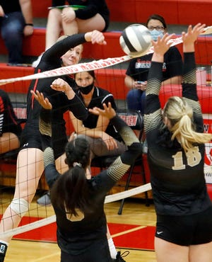Crestview's Autumn Bailey (11) hits a shot at the net against South Central's Brie Schell (18) during high school volleyball action Thursday at Crestview High School.