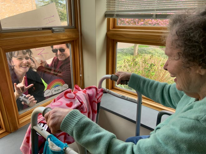 "Rebecca Cordner and her brother Don, during a window visit with their mom, Kathie, on April 19.  Rebecca is signing, ""I love you"" to her mom."