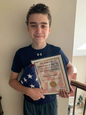 Nicky Christopher, 12, of Lower Makefield, holds an American flag presented to him by Rep. Brian Fitzpatrick.