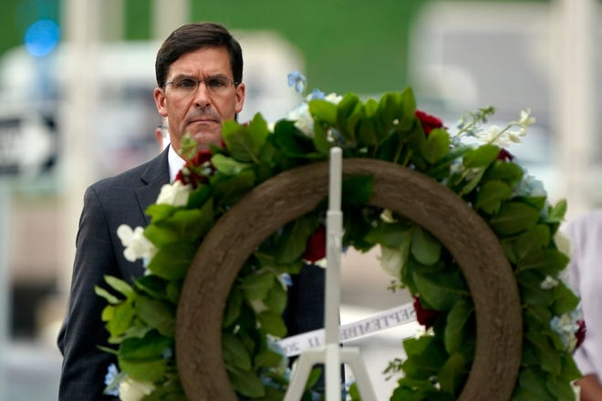 On Sept. 11, 2020, Defense Secretary Mark Esper lays a wreath during a ceremony at the National 9/11 Pentagon Memorial to honor the 184 people killed in the 2001 terrorist attack on the Pentagon. President Donald Trump fired Esper on Nov. 9.