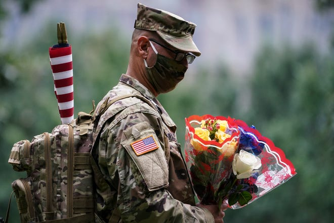 US Army Sgt. Edwin Morales arrives to place flowers for fallen New York City firefighter Ruben D. Correa at the National September 11 Memorial and Museum in New York on Friday.  The names of nearly 3,000 victims of the Sept. 11, 2001, terror attacks will be read by family members at a ceremony organized by the Tunnel to Towers Foundation.  (AP Photo/John Minchillo)