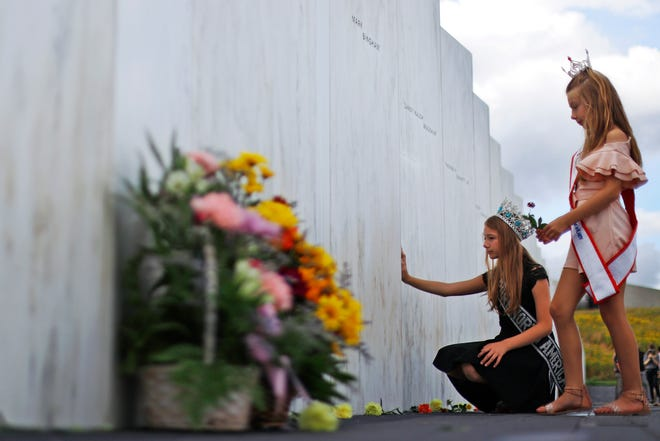 Mackenzie, right, and Madison Miller from Avonmore, Pa., visit the Wall of Names at the Flight 93 National Memorial in Shanksville, Pa., on Thursday, a day before the 19th anniversary of the Sept. 11, 2001, terrorist attacks. The Wall of Names honors the 40 people killed in the crash of Flight 93. (AP Photo/Gene J. Puskar)