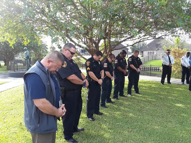 Attendees bow their heads in prayer Friday at Roger Songe Veterans Memorial Park in Houma during the Sept. 11 anniversary.