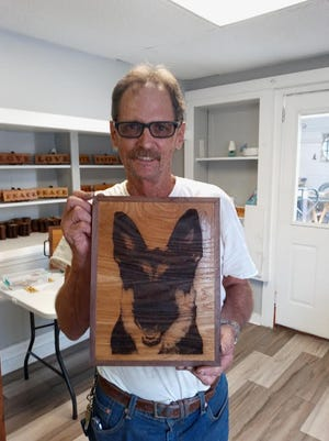 Douglas Olson holds a wall hanging of his dog, Piper.