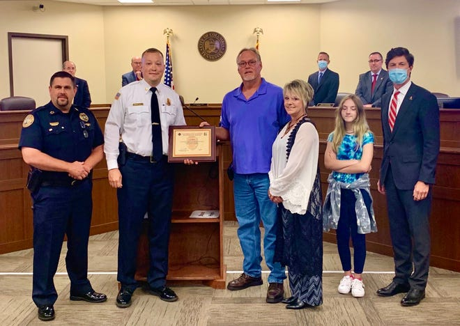 Retired Columbia firefighter Lon Osmon, center, is presented with the Good Samaritan Award for his heroic duties in July when he saved the life of a local 3-year-old boy. Osmon was given the award during Columbia City Countil's regular meeting Thursday, Sept. 10, 2020. (Photo by Kellye Murphy/City of Columbia)