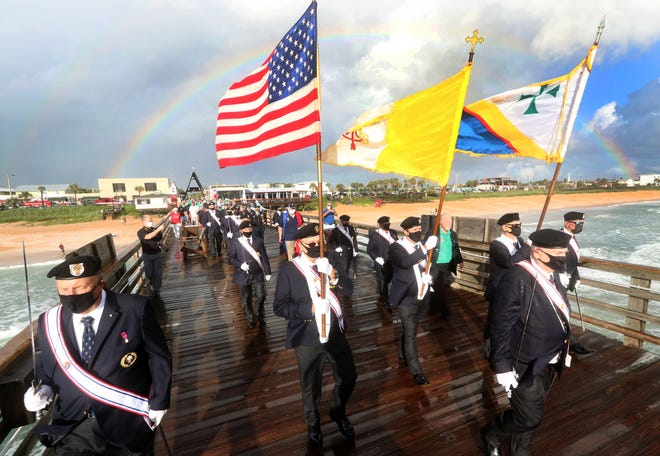 Members of the Knights of Columbus lead the procession out on the Flagler Beach Pier on Friday, for the Sept. 11 ceremony as a rainbow from a passing storm hangs overhead in the background.