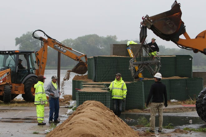 City of Burlington workers remove flood barriers along the Mississippi River Friday near the Port of Burlington. The workers were removing the barriers to make way for the start of construction of the latest section of the flood wall.