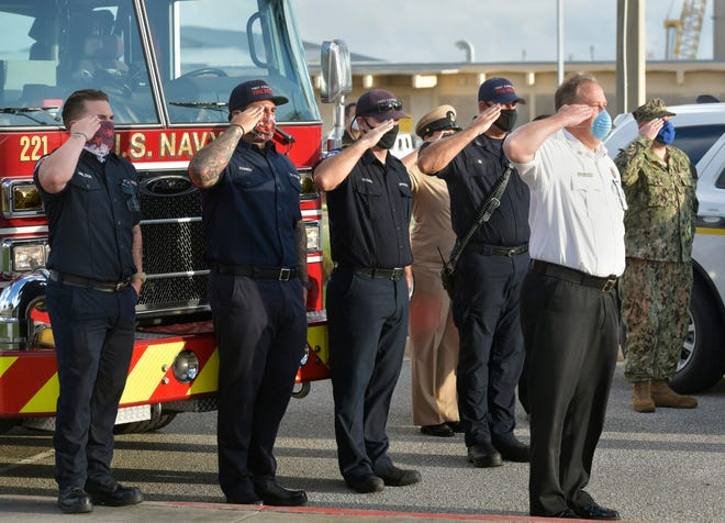 Members of the First Coast Navy Fire Rescue Department and the Security Department Mayport salute the raising of the flag during a 9/11 remembrance ceremony Friday at Mayport Naval Station in Jacksonville. The ceremony commemorates the terrorist attacks on the country on Sept. 11, 2001.