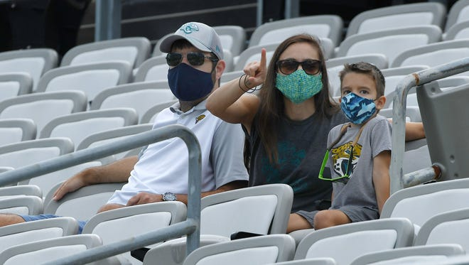 "A family watches a Jaguars scrimmage on Aug. 29 at TIAA Bank Field. Fans will be required to wear masks inside the stadium for Jaguars home games and seat ""pods"" will be distanced from other fans."