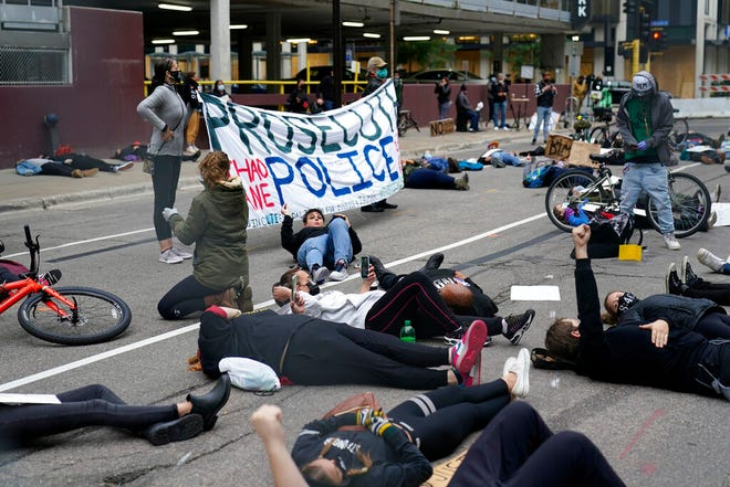 Protesters hold a die-in outside the Hennepin County Family Justice Center where four former Minneapolis police officers appeared at a hearing Friday in Minneapolis. The officers are charged in the death of George Floyd who died in police custody in May.