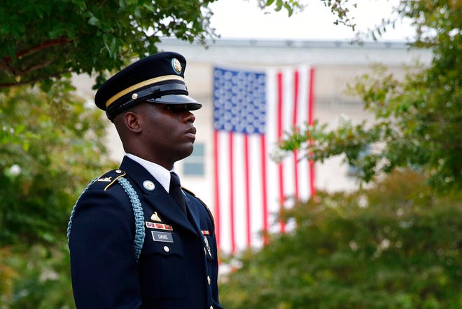 In this Sept. 11, 2019, file photo, a member of the U.S. Army Old Guard stands on the grounds of the National 9/11 Pentagon Memorial before a ceremony in observance of the 18th anniversary of the September 11th attacks at the Pentagon in Washington. On Sept. 11, 2020, Americans will commemorate 9/11 with tributes that have been altered by coronavirus precautions and woven into the presidential campaign.