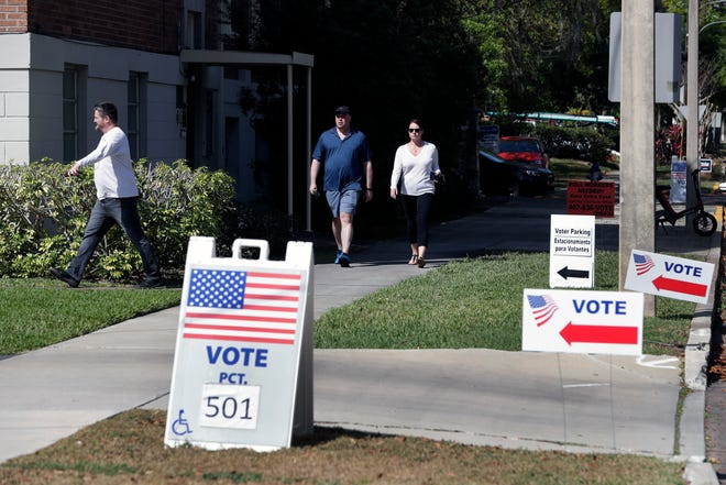 In this March 17 file photo, voters head to a polling station to vote in Florida's primary election in Orlando. Florida felons must pay all fines, restitution and legal fees before they can regain their right to vote, a federal appellate court ruled Friday.