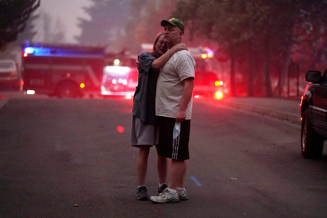 A couple, who declined to give their names, embrace while touring in an area devastated by the Almeda Fire, Thursday in Phoenix, Ore.